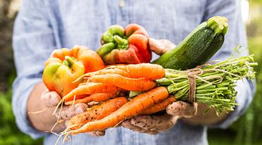 Mann hält Gemüse in der Hand